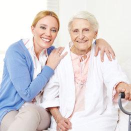 female caregiver and senior woman smiling