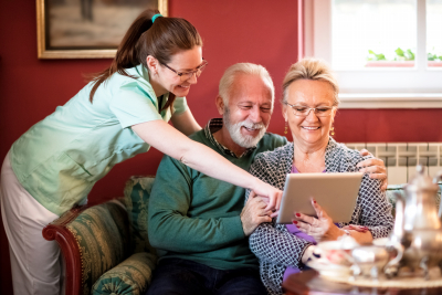 smiling nurse showing patients how to use tablet at nursing home