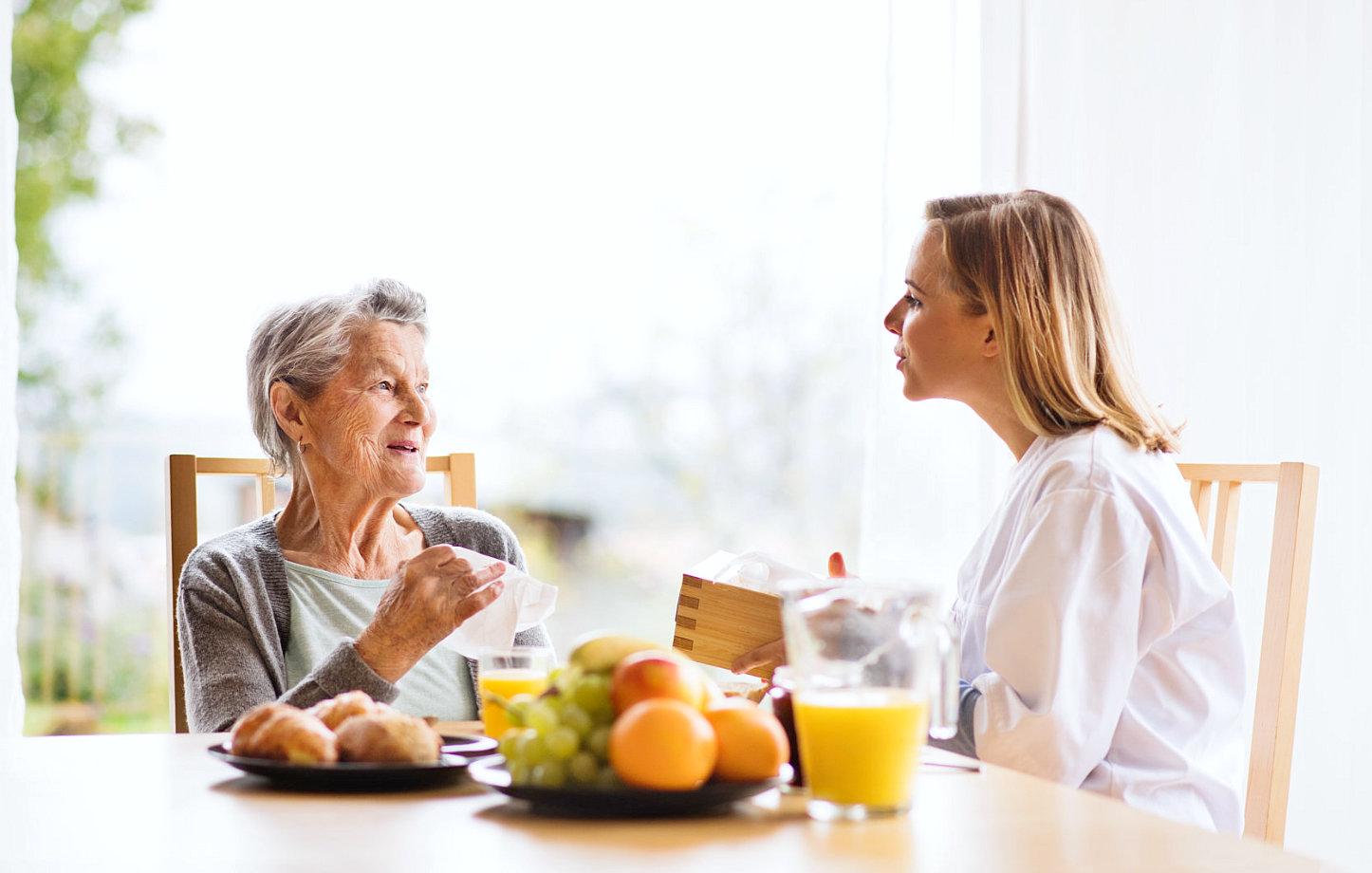 female caregiver and senior woman talking